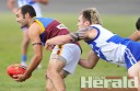 Forrest defender Brendan Hunter gets his handball away as South Colac forward Ben Cox attempts to lay a tackle at Joiner Reserve.
