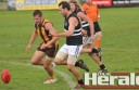 Apollo Bay's Josh Cooper and Lorne's Rick White chase a loose ball during their teams' Easter clash at Apollo Bay Recreation Reserve, which attracted twice the club's regular crowd