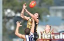 Colac Tiger Ryan Monaghan flies high over teammate Kaden Newton and Lara's David Isbister