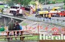Onlookers watch as workers right a crashed semi-trailer on a bridge at Winchelsea.