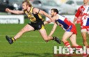 Colac Tigers midfielder Kane Smartt kicks for goal ahead of Geelong West-St Peters player Scott Frangos.