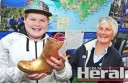 Colac's Angus Rogers trades a Golden Gumboot he found on the Old Beechy Rail Trail for tickets to Kidz Kingdom. He is pictured with Colac Visitor Centre's  Robyn Perrin.