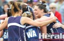 Colac Imperials skipper Bec Scott, right, celebrates the Cats' third straight premiership with teammates.