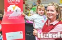 Emily Davis helps her daughter Shilah, 3, post a letter to Santa at Colac's post office.