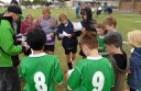 Colac Otway Junior Rovers players, pictured with coach Darren Balboni, sing the song after their win in the club's debut match in FFV Geelong-region's under-13 competition.