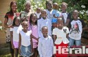 Colac's Lual family, including four children orphaned in Uganda more than three years ago, are spending the summer holidays together in Colac. Back from left, Rebecca, Nyibol, Anna, Sarah, Noah, Ben, John, centre row from left, Amol, Nyanduor, Akuot, Makuol, Sara, and, front, Moses.