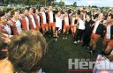 FULL OF VOICE: Birregurra senior footballers and Saints supporters belt out the club's song on Central Reserve following their thrilling grand final win against South Colac.